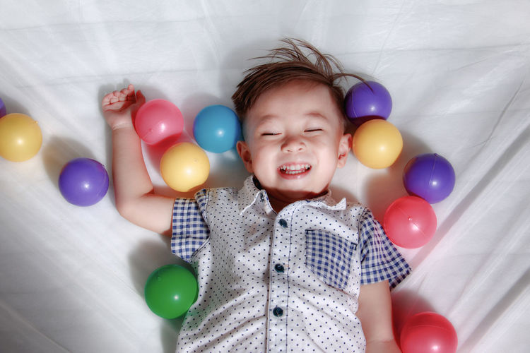 High angle view of boy playing with balloons while lying on bed at home