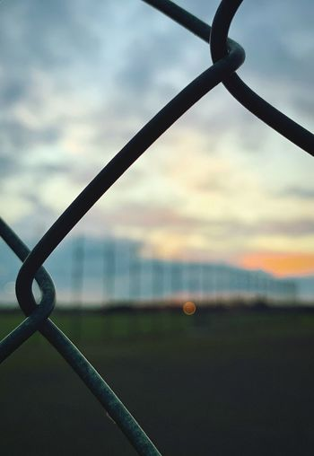A fence Cloud - Sky Sky Security Protection Safety Fence Chainlink Fence Metal Barrier Focus On Foreground No People Boundary Nature Close-up Outdoors Day Sunset Land The Photojournalist - 2019 EyeEm Awards The Mobile Photographer - 2019 EyeEm Awards