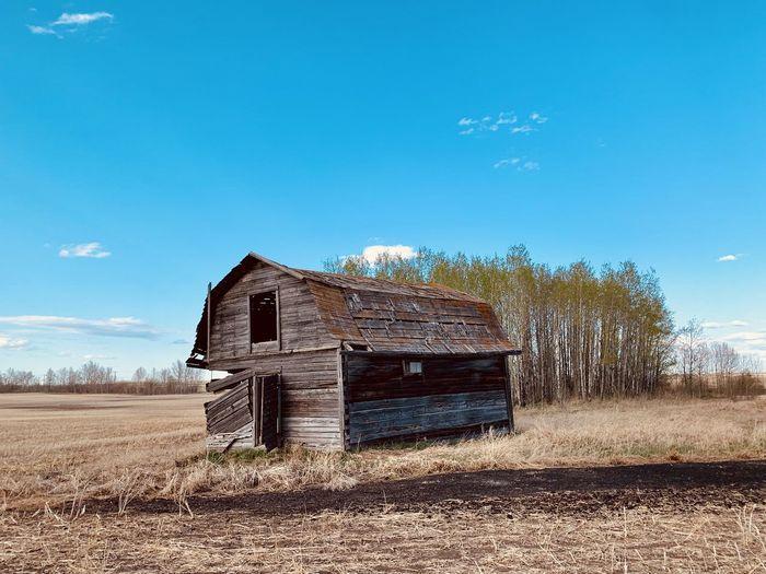 Old barn on field against blue sky