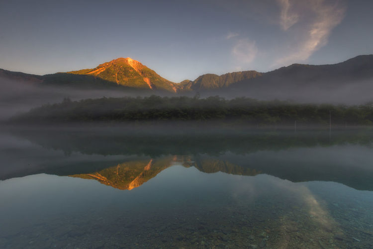 Taisho Ike Pond, Japan Japan Taishoike Lakeside Beauty In Nature Cloud - Sky Hazy  Idyllic Kamikochi Lake Mountain Mountain Peak Mountain Range Nature No People Non-urban Scene Outdoors Reflection Reflection Lake Remote Scenics - Nature Sky Tranquil Scene Tranquility Water Waterfront