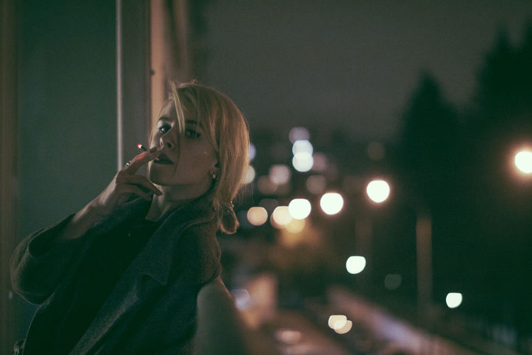 Smoking Leisure Activity Contemplation Hairstyle Looking Away Adult Headshot Focus On Foreground Looking Women Hair Beauty Beautiful Woman Lifestyles Real People Portrait Blond Hair Night Young Adult Young Women One Person Illuminated