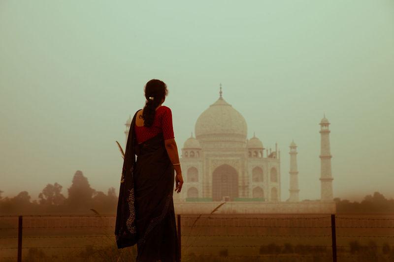 Rear view of woman standing against taj mahal