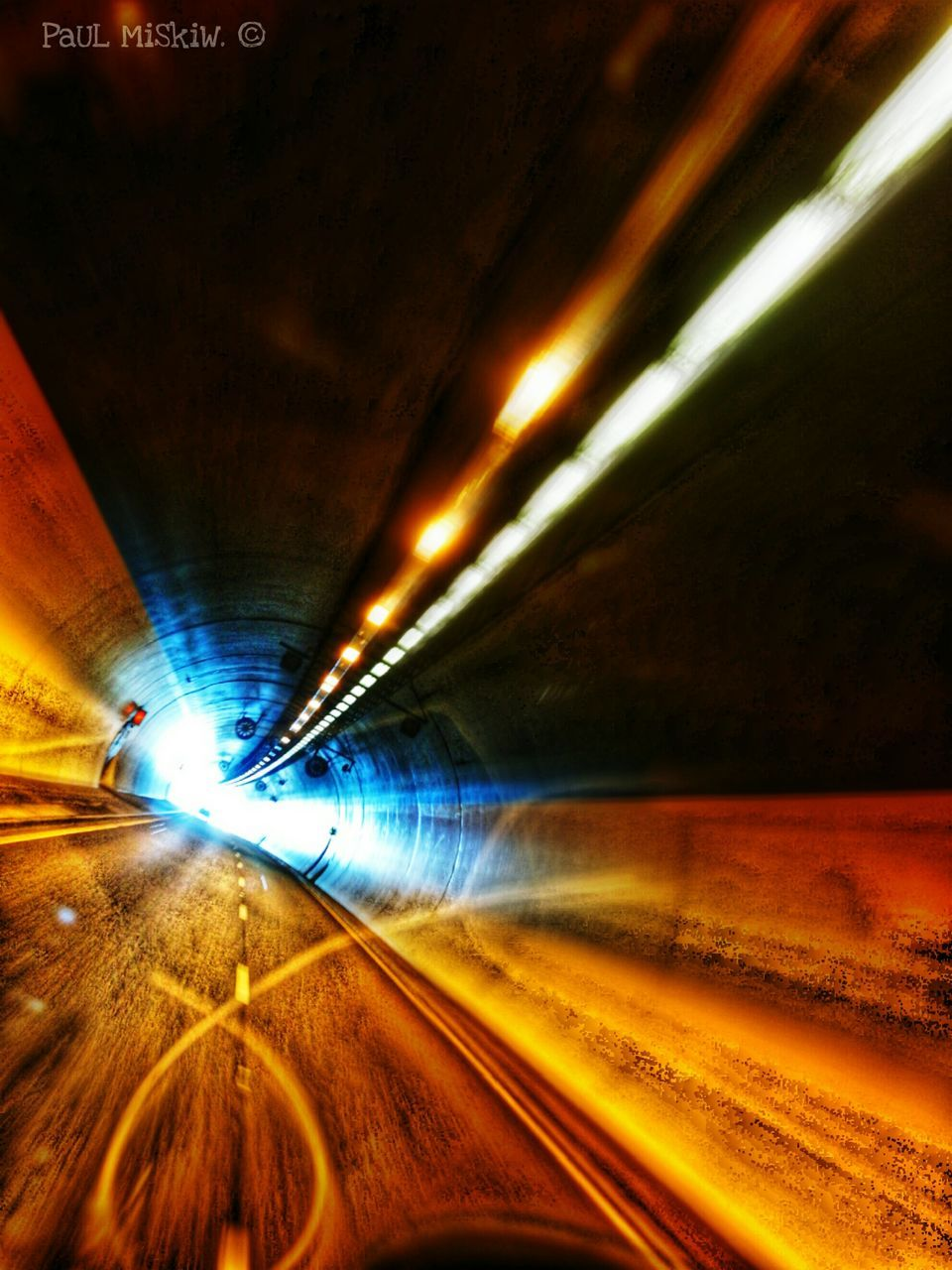 illuminated, transportation, the way forward, tunnel, diminishing perspective, speed, road, night, underground, rail transportation, motion, mode of transport, light trail, curve, railroad track, no people, indoors