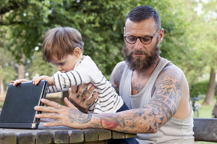 Father and son holding laptop while sitting outdoors