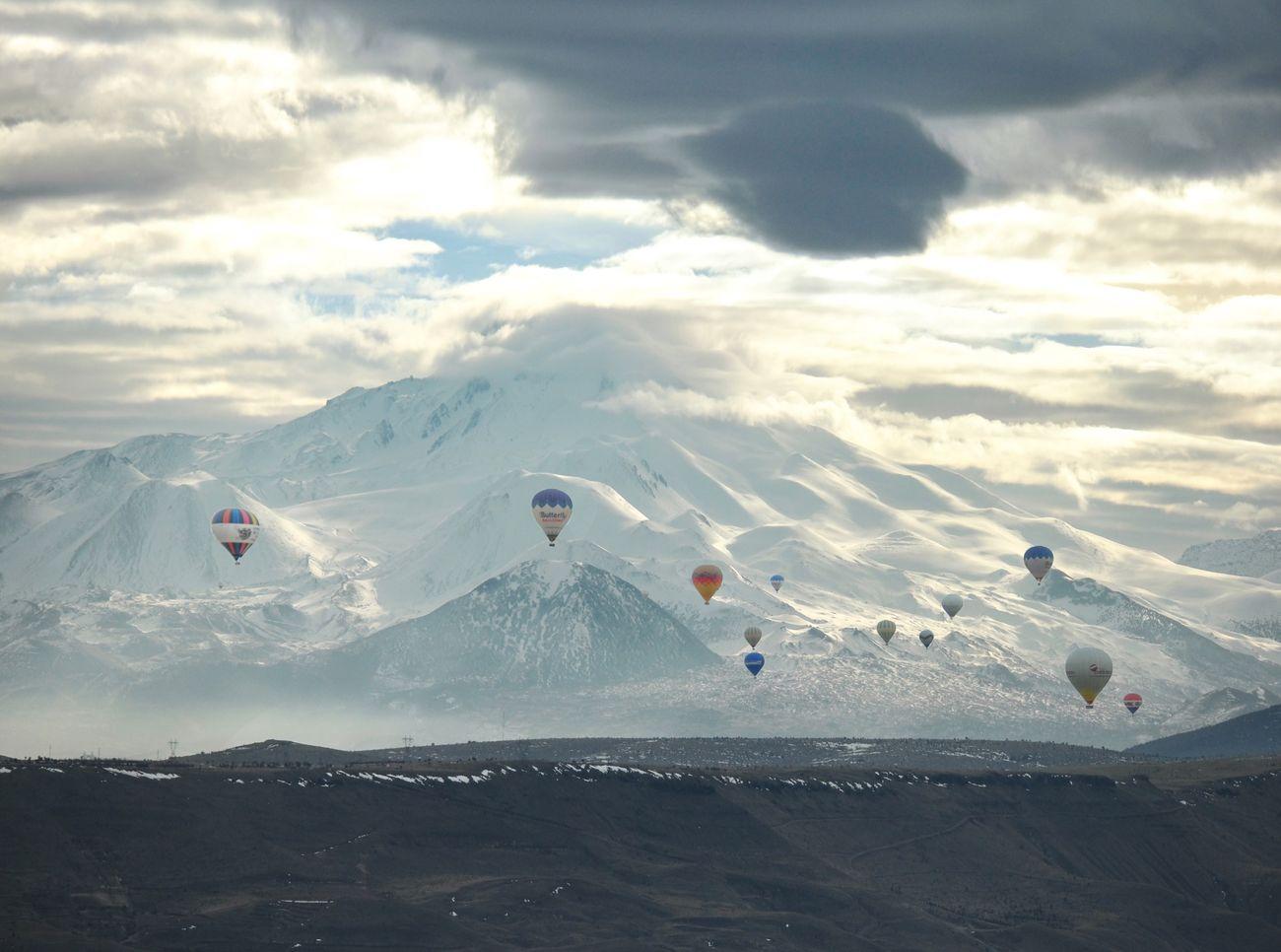 Hot air balloons flying against sky at cappadocia during sunrise