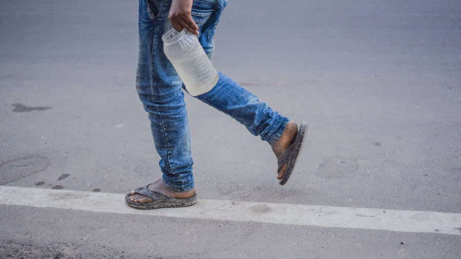 Low section of man carrying water in plastic bottle while walking on road
