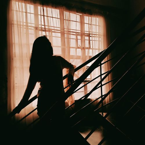 Silhouette woman standing by window at home
