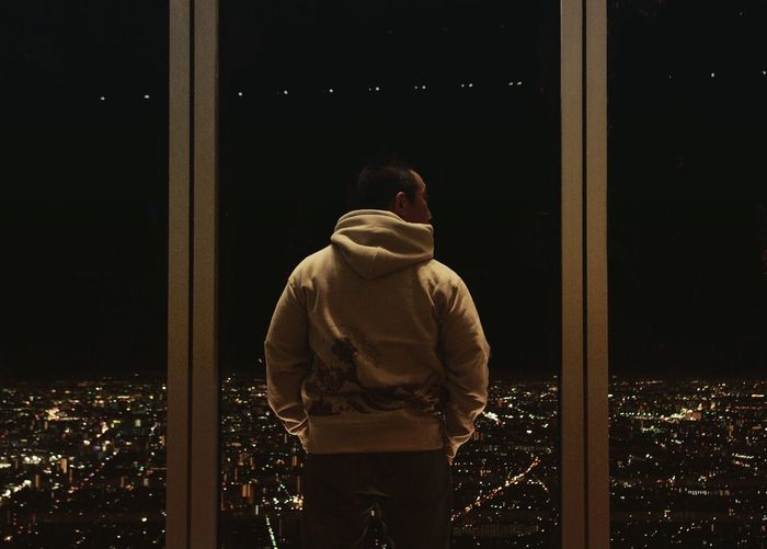 Rear view of man looking at illuminated city from window