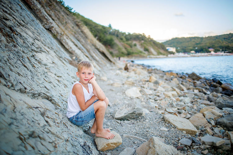 Boy sitting on rock at shore