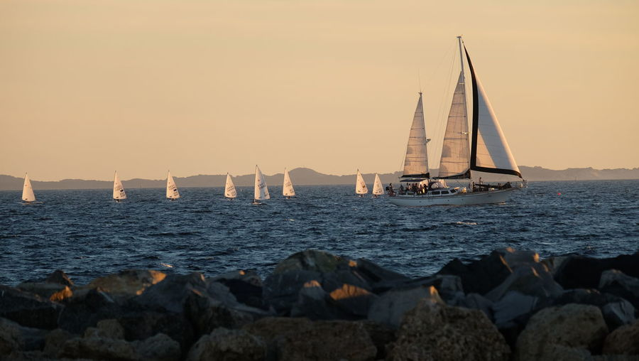 Sailboats Sailing In Sea Against Clear Sky During Sunset