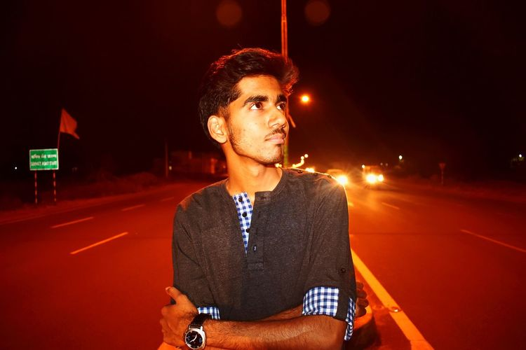 Thoughtful Young Man Looking Away While Standing On Road At Night