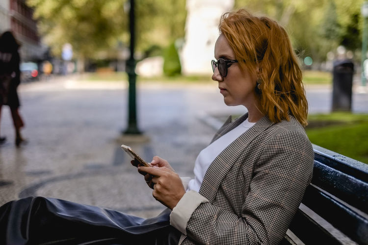 Young woman using mobile phone on bench