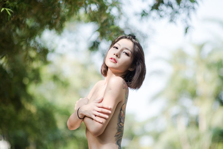 Side View Portrait Of Shirtless Young Woman Standing At Park