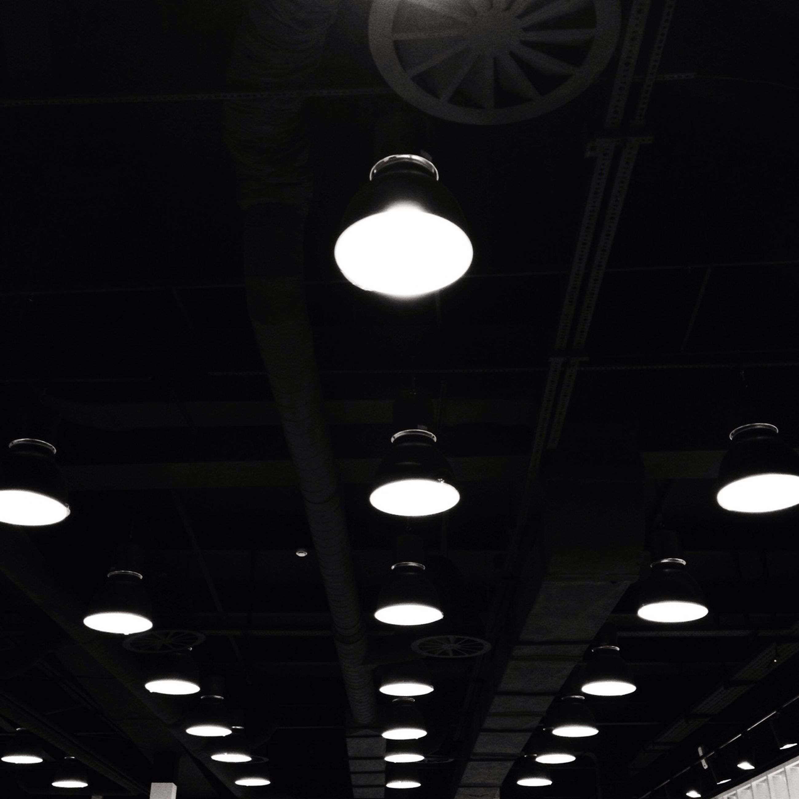 illuminated, indoors, ceiling, lighting equipment, low angle view, electric light, architecture, electricity, built structure, hanging, electric lamp, night, in a row, pendant light, light - natural phenomenon, light bulb, lamp, light fixture, modern, technology