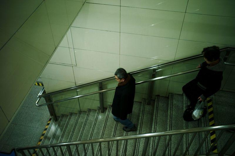 High angle view of people walking on escalator
