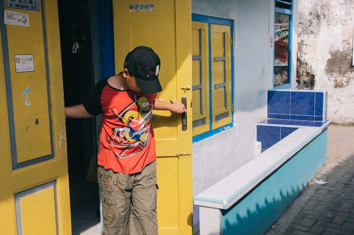 Architecture Boys Building Exterior Built Structure Casual Clothing Day Leisure Activity Lifestyles Mobile Phone One Person Outdoors People Portable Information Device Real People Standing Streetphotography Technology Three Quarter Length Vending Machine Wireless Technology Young Adult Paint The Town Yellow