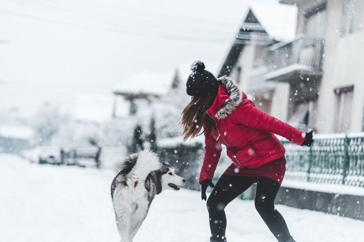 Husky Snow Winter Cold Temperature Warm Clothing One Person Clothing Real People Women Snowing Lifestyles Built Structure Day Architecture Nature Focus On Foreground Leisure Activity Building Exterior Motion Outdoors Extreme Weather