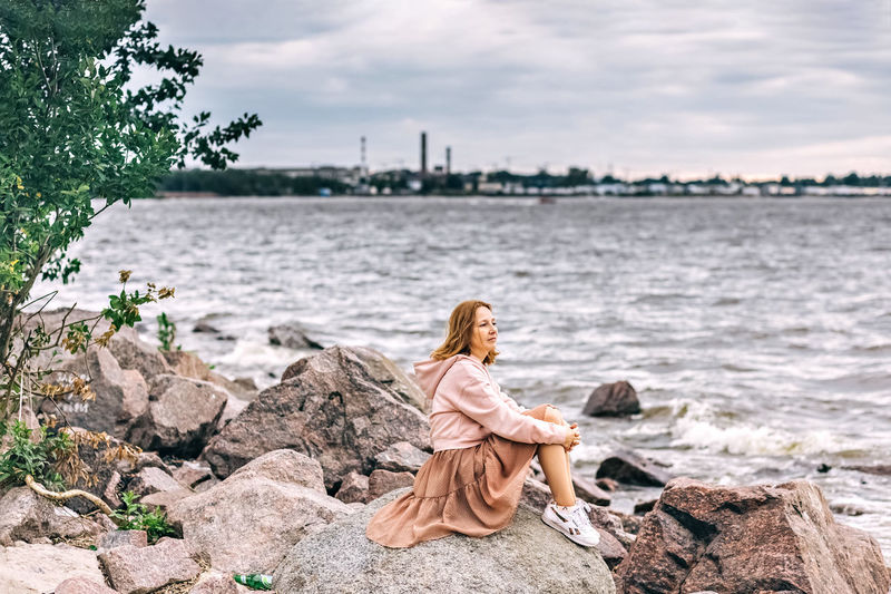 Rear view of woman sitting on rock looking at shore against sky