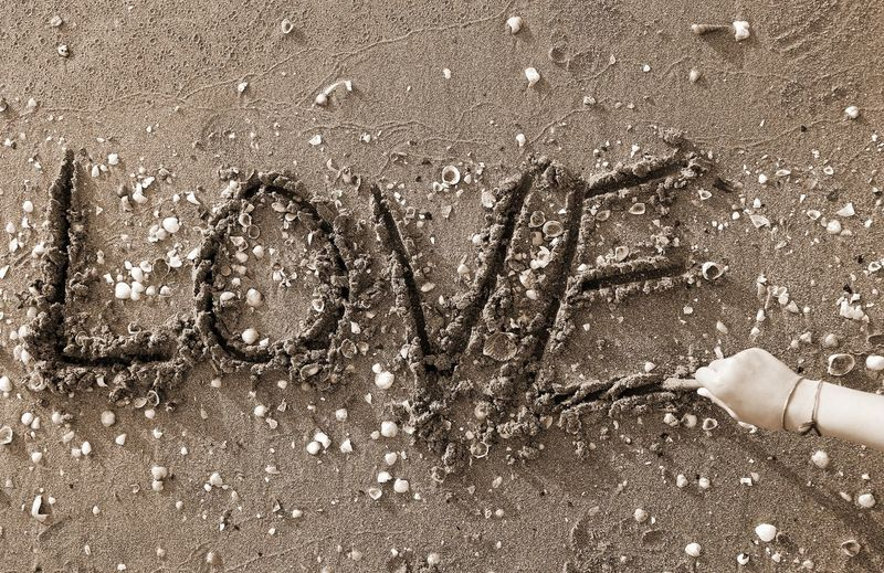Cropped Hand Writing Love Text At Beach