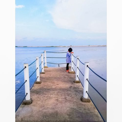 Girl standing by railing against sea and sky