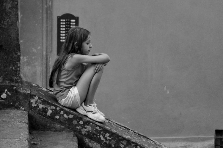 Side view of a girl sitting on ground