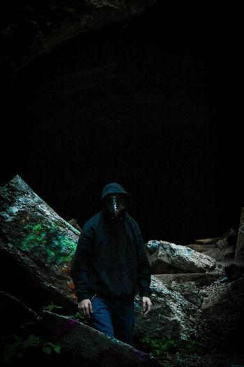 Man standing on rock at night
