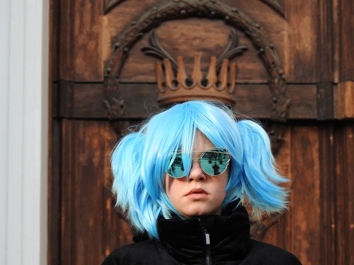 Portrait of girl with dyed hair wearing sunglasses against door