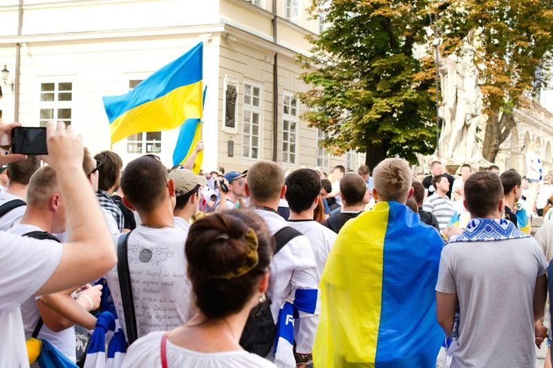 People protesting on street with ukrainian flag