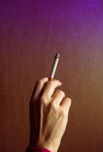 Close-up of hand holding cigarette