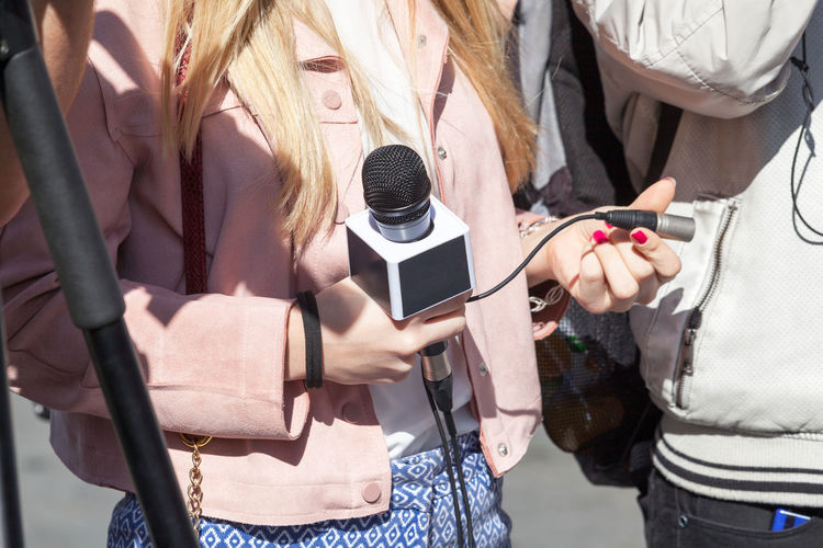 Journalist Holding A Microphone Advertising Interview Interview Time MarketingCommunications PR Press Production Reporting Live  Unrecognizable People Broadcasting Input Device Mass Media Media Coverage Media Equipment Microphone News News Conference Outdoors Press Conference Real People Reporters Sideline Reporters Young Woman At Work