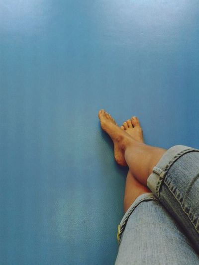 Low Section Of Person Legs On Blue Wall