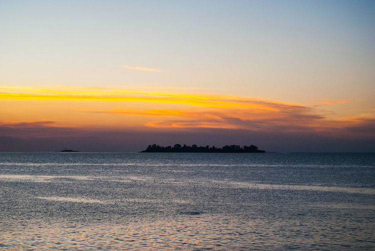 An island in the horizon during sunset. Sky Water Scenics - Nature Sea Beauty In Nature Sunset Tranquil Scene Tranquility Waterfront Horizon Idyllic Horizon Over Water Orange Color Cloud - Sky No People Nature Land Beach Outdoors Island Horizontal Copy Space