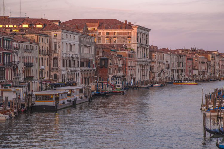 Boats in canal by buildings in city against sky during sunset