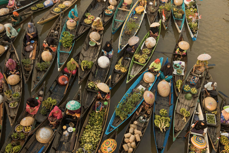 Aerial view of people in boat by vegetables for sale in market
