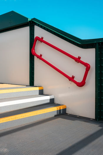 A minimal photo of a clear blue sky and colourful steps and handrail.