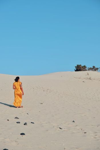 Rear view of woman on desert against clear sky