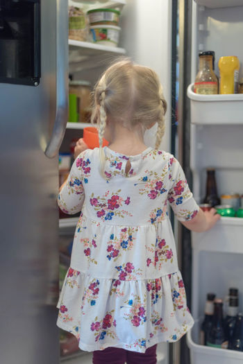 Rear view of girl standing by refrigerator