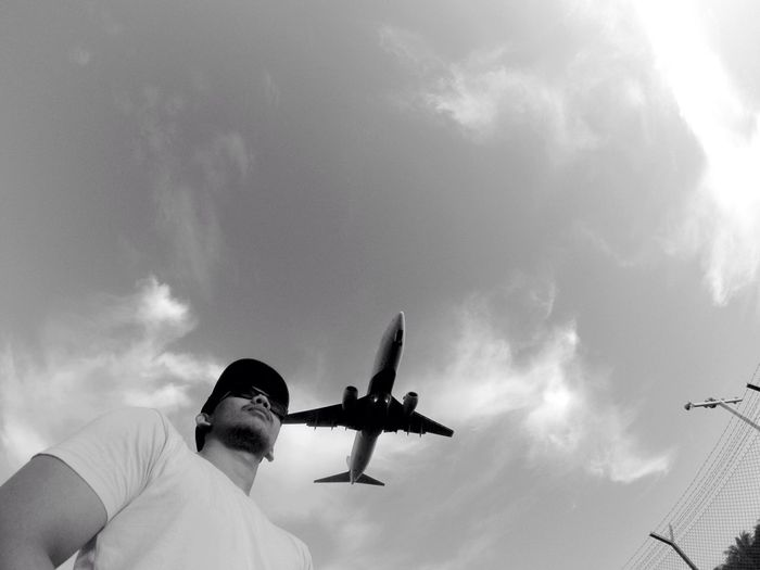 Low angle view of man by airplane flying against cloudy sky