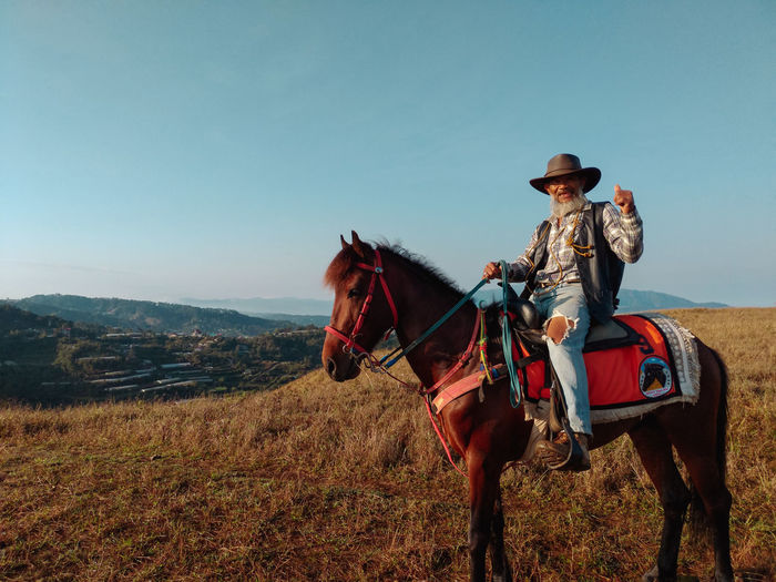 Horseback riding on the top of Mt. Yangbew at La Trinidad, Benguet. Mt. Yangbew is just a 30-minute trek and is best to be visited on Sunsets or sunrise Mobilephotography Mobile Photography Portrait Portraiture Philippines EyeEm Best Shots Eyeem Philippines La Trinidad, Benguet Mt. Yangbew Wild West Working Rural Scene Cowboy Hat Cowboy Hat Horse Sky Horseback Riding The Traveler - 2019 EyeEm Awards The Mobile Photographer - 2019 EyeEm Awards The Great Outdoors - 2019 EyeEm Awards The Portraitist - 2019 EyeEm Awards My Best Photo