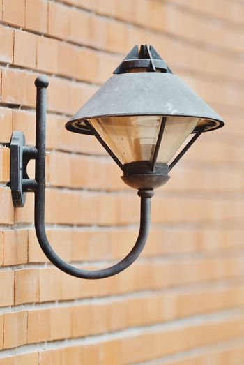 Close-up of street light against on brick wall