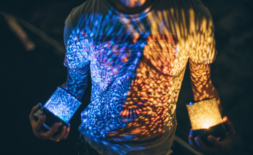 Midsection Of Man Holding Illuminated Lights In Dark