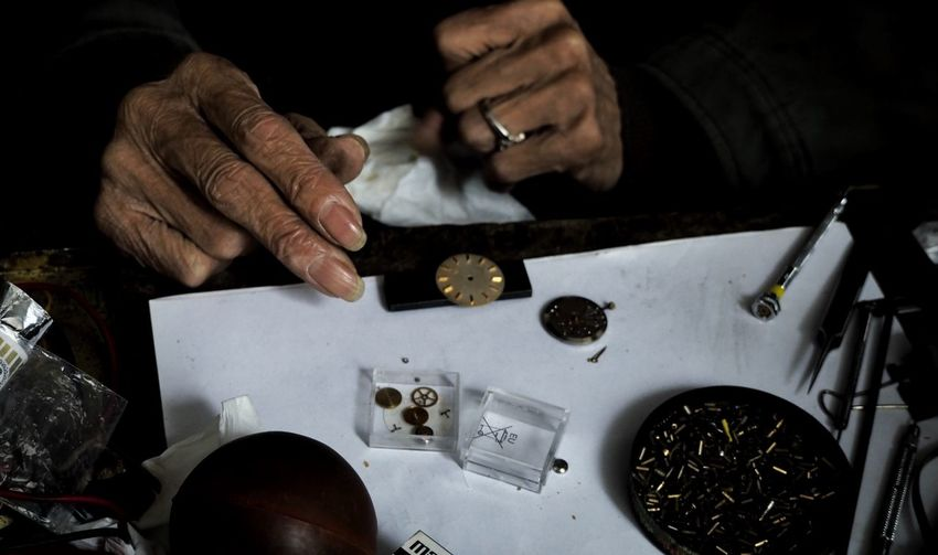 Cropped Image Of Wrinkled Hands Repairing Watch At Table