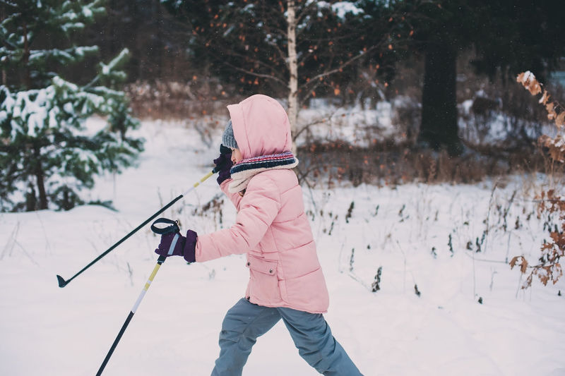 happy child girl skiing in winter snowy forest, spending holidays outdoor. Active winter sports. Winter Cold Temperature Real People Leisure Activity Nature Lifestyles Snow Warm Clothing Winter Wonderland Skiing Child Childhood Winter Sport Candid Woods Forest Outdoors Sport Active Lifestyle  Healthy Lifestyle Holiday Vacations Winter Holidays Christmas Holidays