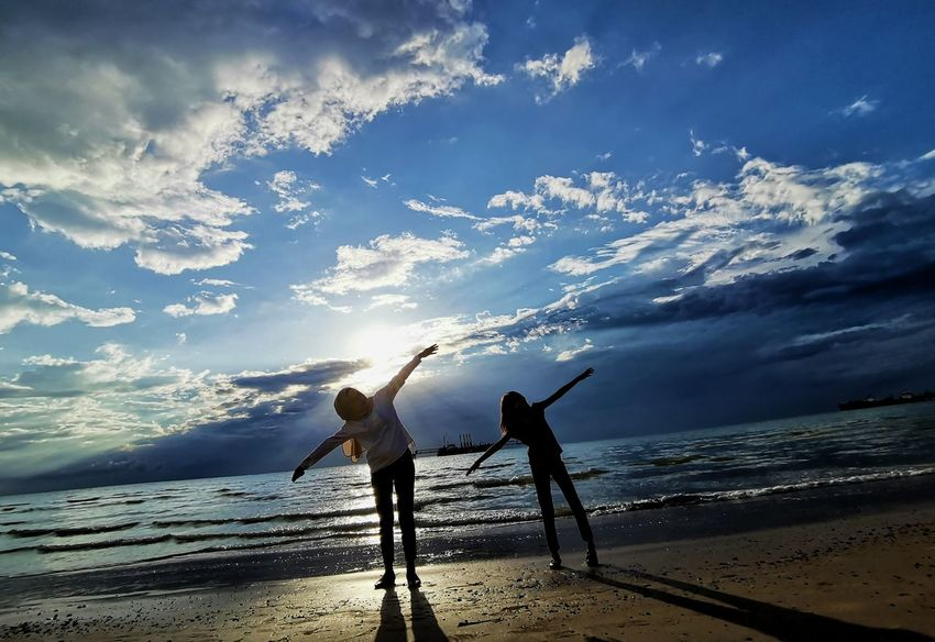 Silhouette. Mother and little girl play at the beach during sunset Sky Beach Water Cloud - Sky Sea Land Horizon Over Water Leisure Activity Beauty In Nature Horizon Two People Real People Togetherness Nature Lifestyles Women Men Scenics - Nature Standing Outdoors Human Arm Arms Raised