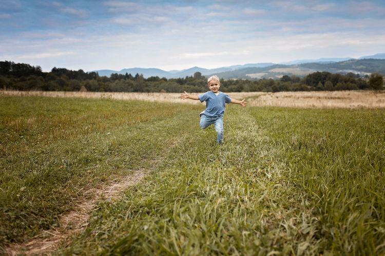 Full length of happy girl on field against sky