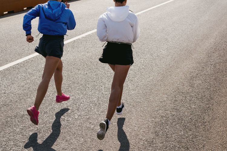 High angle view of female friends jogging on road