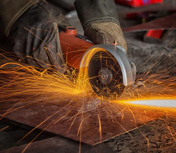 Close-up of man cutting metal at factory
