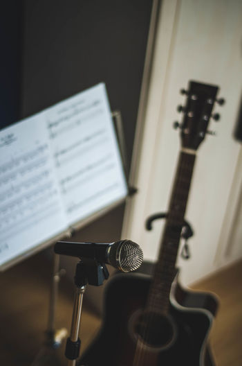 Close-up of microphone with musical note and guitar in background