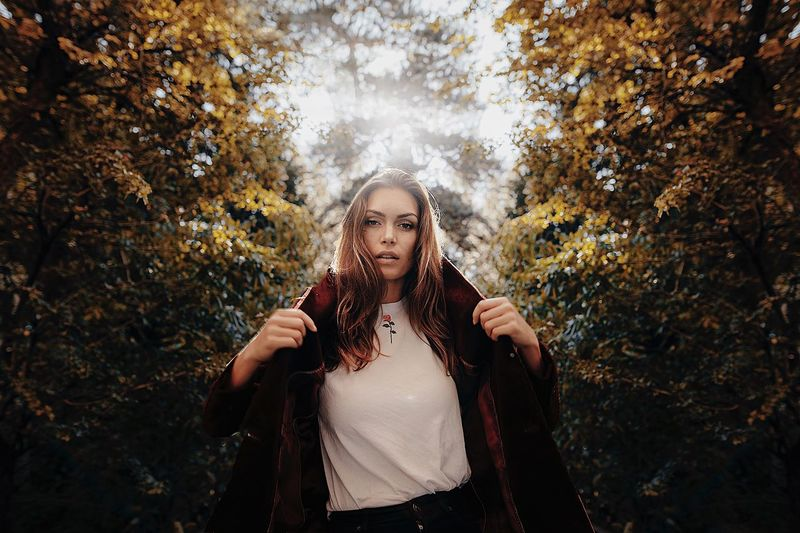Young woman standing in park during autumn