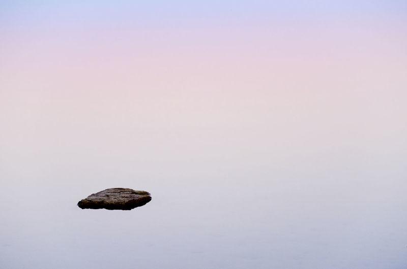 Idyllic Shot Of Rock In Lake Under Foggy Weather